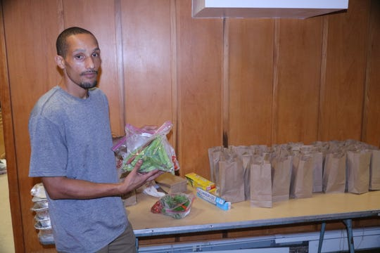 Walter Herres, Executive Director and CEO of Supporting Homeless Innovatively Loving Others (SHILO) packs bag lunches for distribution at the Reformed Church of Highland Park.