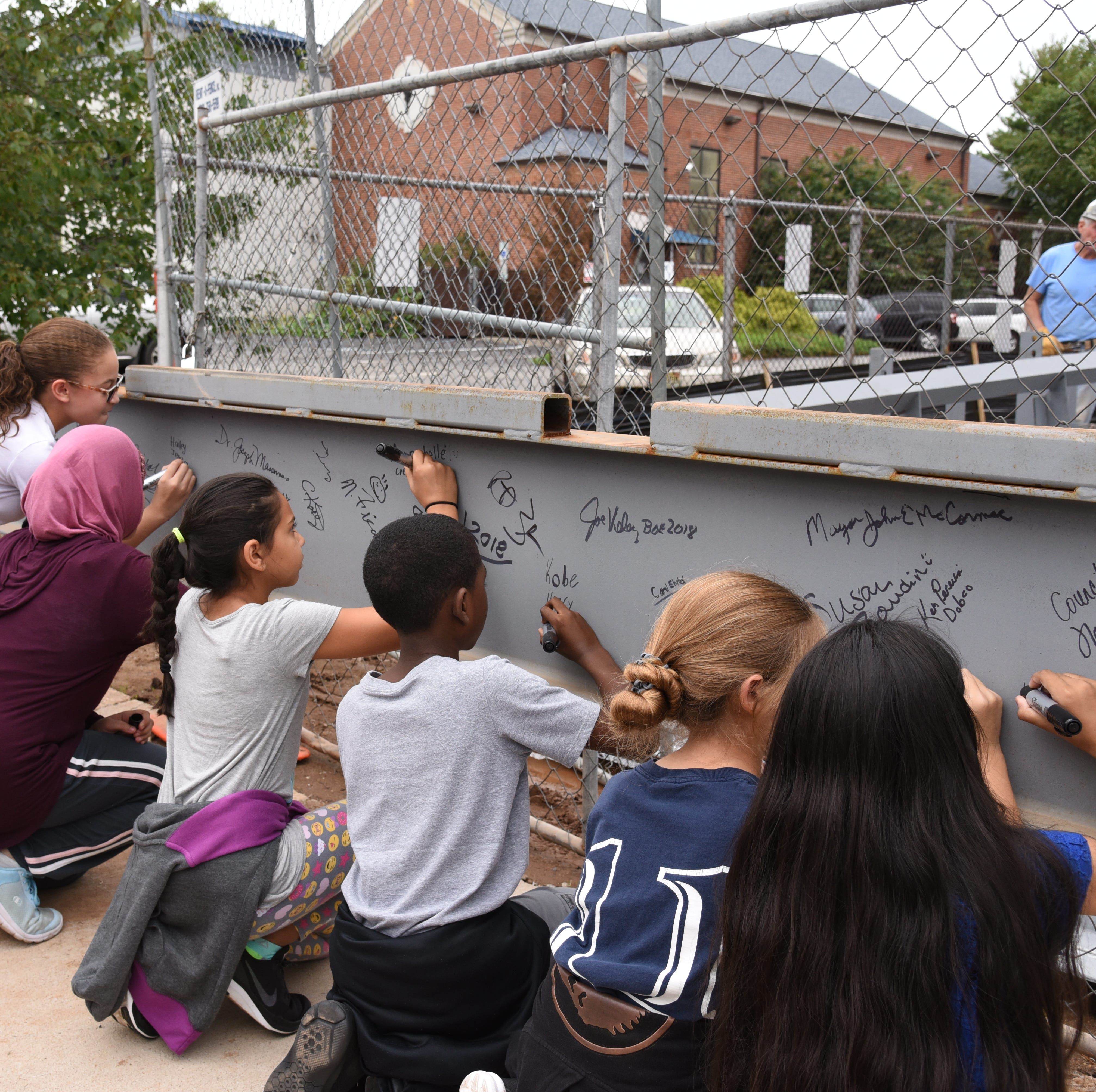 Participants in the Ross Street School #11 'Topping-Off' ceremony signed the  structural steel beam before being hoisted into place and secured atop the buildings frame.