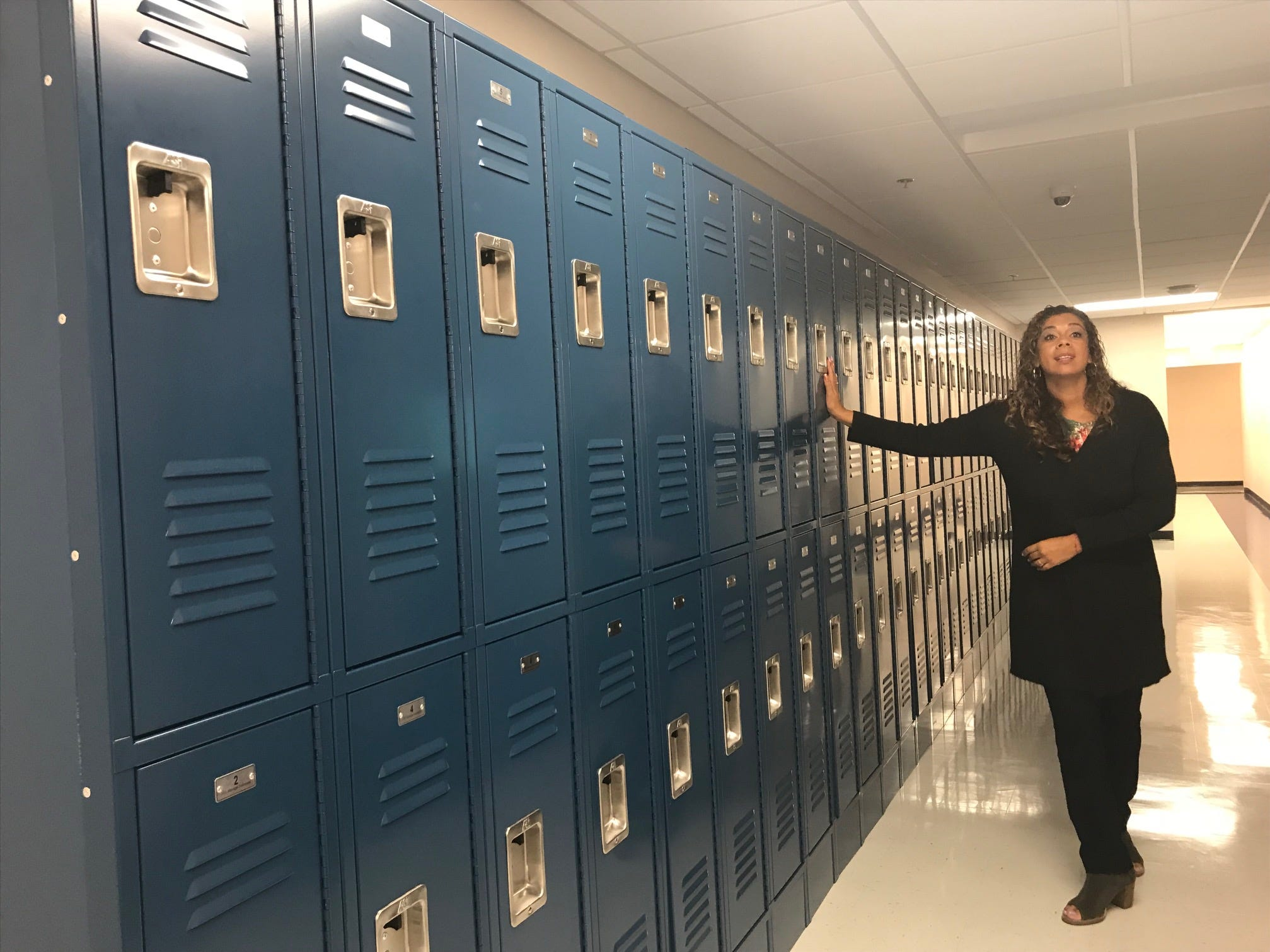 College Achieve Public School (CAPS) Executive Director Rachelle Nelson checks out the new lockers. With fresh, bold blue paint on its pristine walls, College Achieve CentralHigh School welcomed its first students Aug. 27. More than 300 students from Somerset, Middlesex and Union countieshave been enrolled in the charter high school.