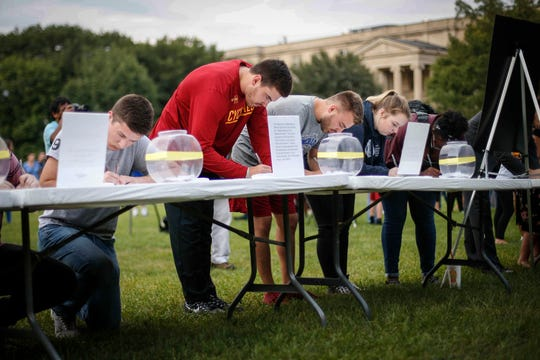 Iowa State students and friends of Celia Barquin Arozamena leave personal notes for the parents of their fellow student during a vigil on Wednesday, Sept. 19, 2018, in Ames.
