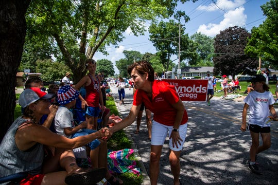 Iowa Governor Kim Reynolds, who is running for election this fall, shakes hands with people watching Windsor Heights Fourth of July Parade on July 4, 2018.