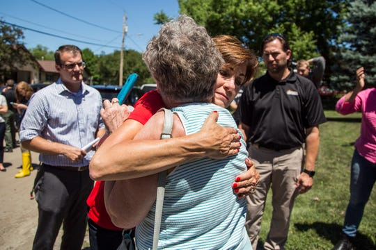 Iowa Governor Kim Reynolds embraces Beverly Phillips, of Des Moines, outside her home while touring flood damaged areas of Polk County on Monday, July 2, 2018, on Des Moines's east side. Phillips' home was flooded by Fourmile Creek on Saturday.
