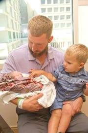 Sampson Shurman, center, holds his newborn daughter, Lilah, with his son Abel, 2.