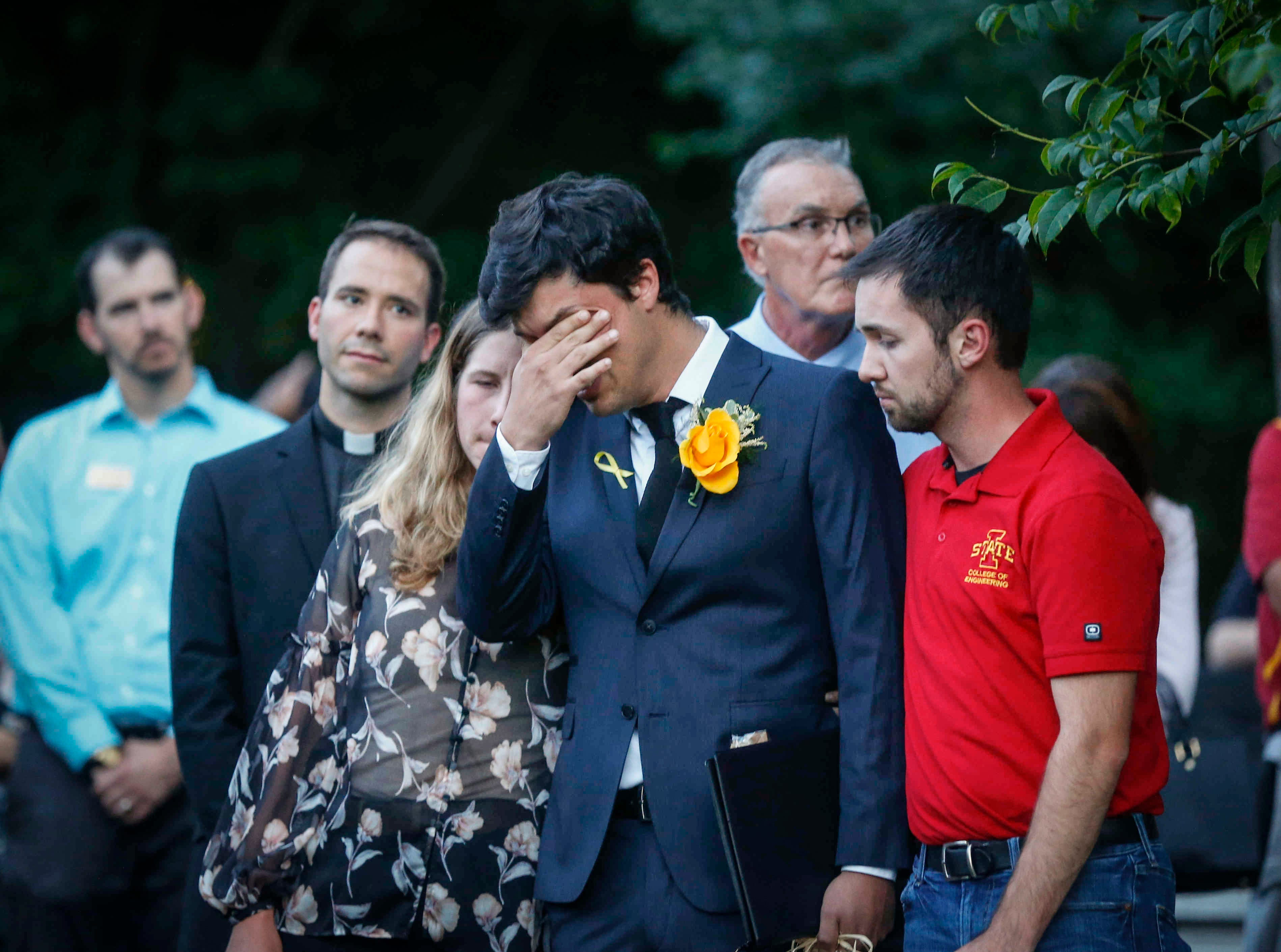 Carlos Negrin Bola–os, boyfriend of Iowa State student Celia Barquin Arozamena, wipes tears as students, faculty and community members mourn Arozamena during a vigil on Wednesday, Sept. 19, 2018, in Ames.