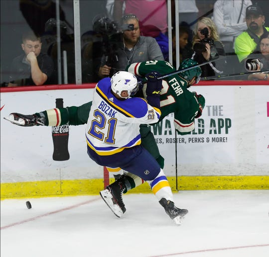 St. Louis Blues center Tyler Bozak, (21) runs Minnesota Wild center Eric Fehr, into the boards as they both chase down a loose puck during the second period of an NHL preseason hockey game, Wednesday, Sept. 19, 2018, in Des Moines, Iowa.