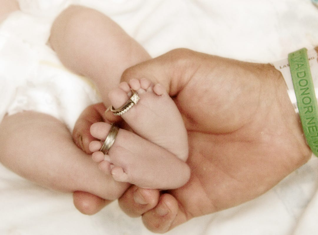 The wedding rings of Sampson and Jessica Shnurman adorn the feet of their newborn daughter, Lilah.