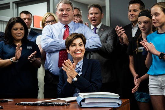 Iowa Governor Kim Reynolds smiles and applauds with the crowd of people around her after she signed a tax bill passed by the Iowa Legislature this session, on Wednesday, May 30, 2018, at MobileDemand in Hiawatha.