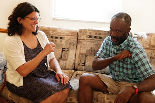 Francis Anwana, 48, who is deaf and has cognitive disabilities, teaches Rashida Tlaib how to sign her name as they visit at the adult foster care home where he lives in Detroit on Monday, September 17, 2018.