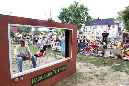 Tyree Guyton with a stuffed Mickey Mouse behind a make-shift TV screen at the Heidelberg art project, the ever evolving art installation on Heidelberg street in Detroit in August 2016.