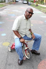 Tyree Guyton poses in the middle of Heidelberg street as a symbolic gesture of taking his project back to it's infancy in August 2016.