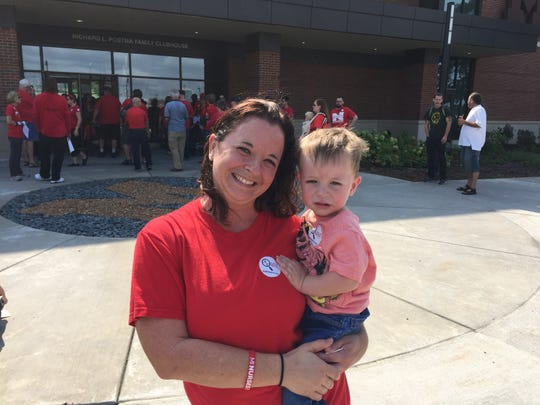 Ruth Moscarello, a 36-year-old labor and delivery nurse from Ypsilanti, carried her 2-year-old son, Nolan, on her hip outside the University of Michigan's monthly regents meeting Thursday, Sept. 20, 2018.