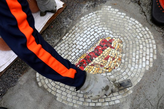 Jim Bachor, 54, of Chicago with the pothole art piece made out of mosaic tile on Alfred street in Eastern Market in Detroit during Murals in the Market on Thursday, Sept. 20, 2018. The piece on Alfred street is a slice of cherry pie.