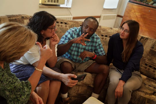 Francis Anwana, 48 who is deaf and has cognitive disabilities, signs to his friend and former teacher Diane Newman, left during a conversation with Anwana's attorney Tania Morris Diaz, right and Rashida Tlaib, second from left in the adult foster care home where Anwana lives in Detroit on Monday, September 17, 2018.