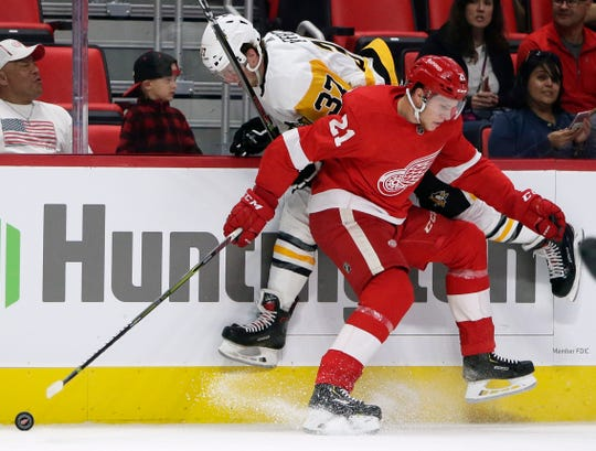 Pittsburgh Penguins center Sam Lafferty (37) is checked against the boards by Detroit Red Wings defenseman Dennis Cholowski (21) during the first period of a preseason NHL hockey game, Wednesday, Sept. 19, 2018, in Detroit.