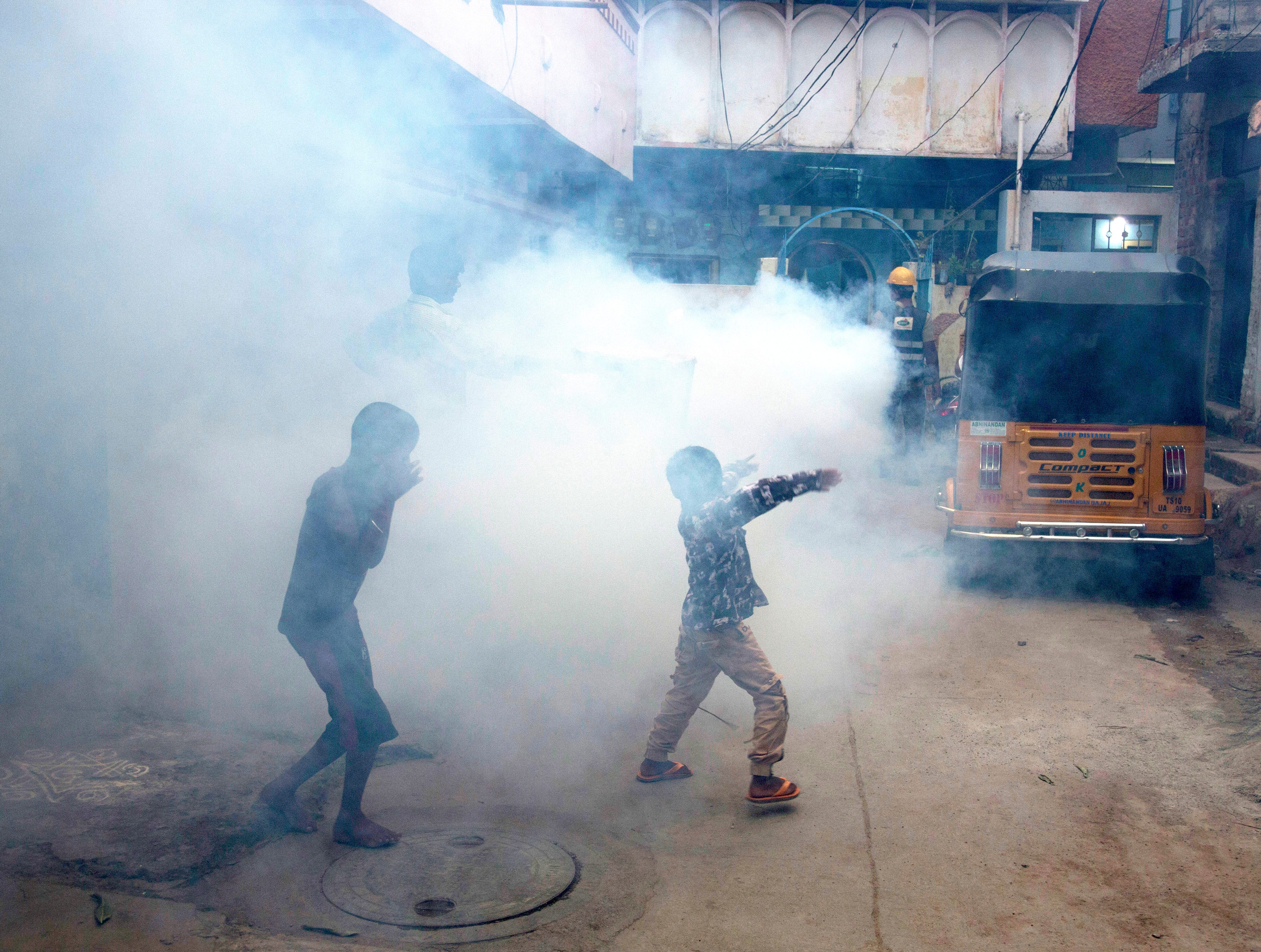 A boy covers his nose as another dances while a health worker fumigates the area outside their house to prevent the spread of mosquito-borne diseases in Hyderabad, India, Thursday, Sept. 20, 2018.