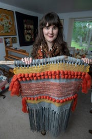 Weaver Julia Targus holds a woven wall hanging in her Plymouth home, September 18, 2018.