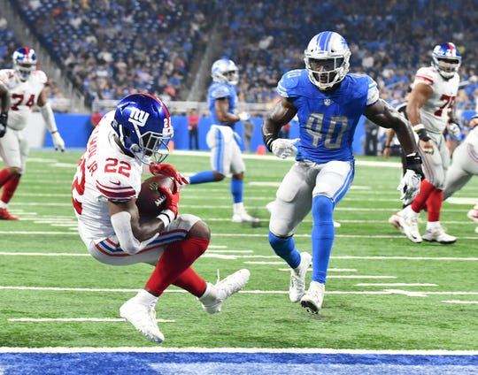 The Giants' Wayne Gallman Jr. (22) steps back into the end zone on a touchdown completion in front of Lions linebacker Jarrad Davis (40) during a preseason game at Ford Field.