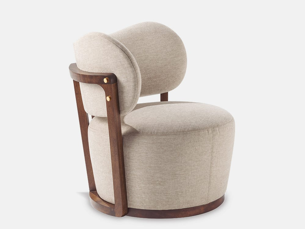 The Rumba upholstered chair designed by Adriana Hoyos features a unique silhouette with pronounced curves and a generous seat. Combining comfort, craftsmanship and design, the chair boasts distinctive details like the gold-finish metal studs on the wooden frame.