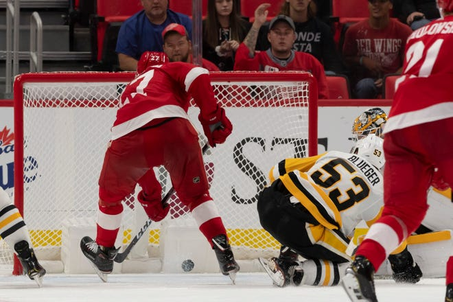 Detroit center Michael Rasmussen send the puck past Pittsburgh goalie Tristan Jarry for the game winning goal in overtime.