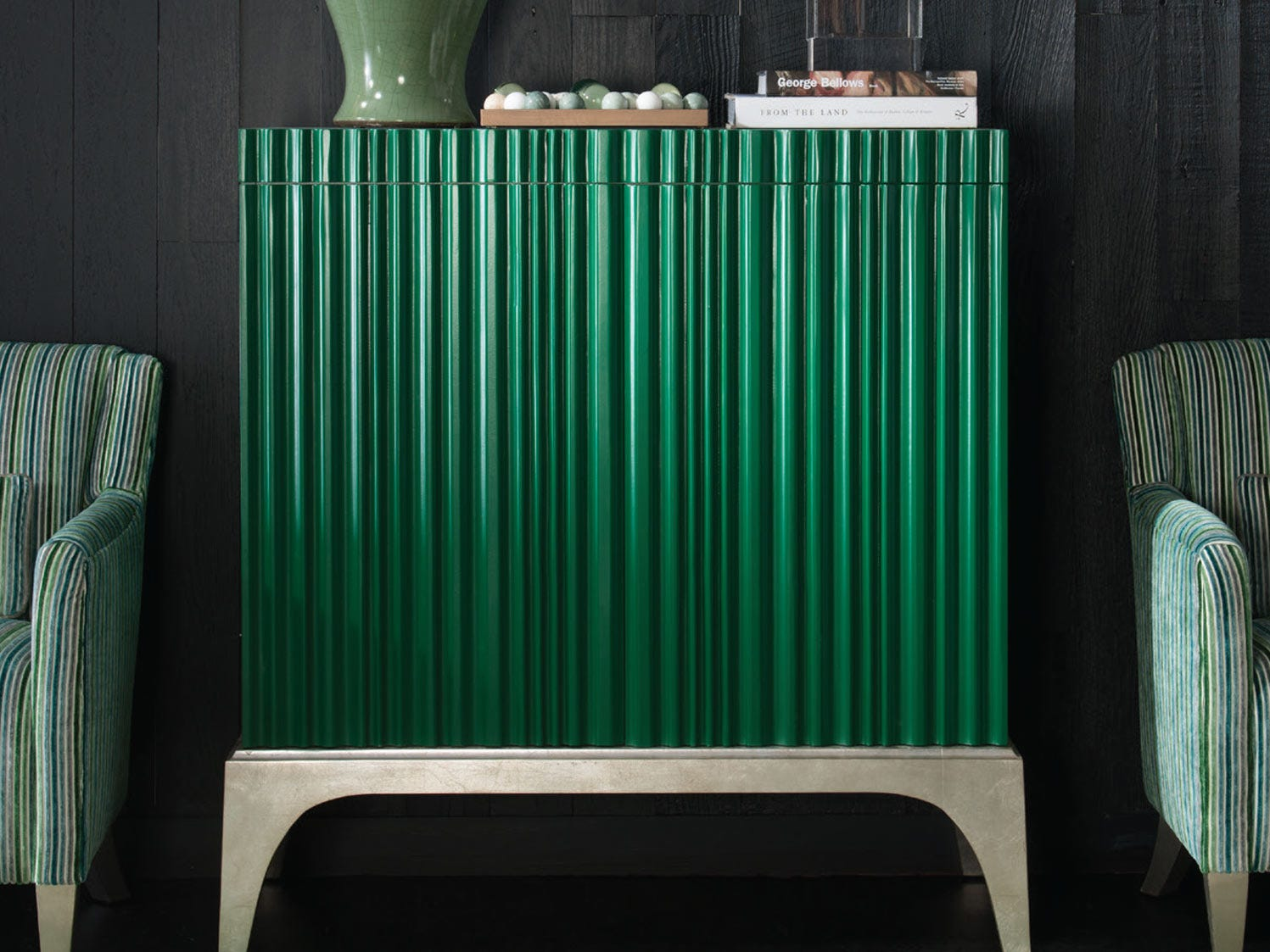 Dazzling emerald green on a piano-ribbed front distinguish the statement Margot Chest from Bruce Andrews. It rests on a silver leaf covered solid maple base, with legs contoured in shape. With beautiful proportions, the 40 3/4-inch-wide piece, handcrafted in America, is 18 3/4 inches deep and stands up from its 12-inch leg an additional 44 inches.