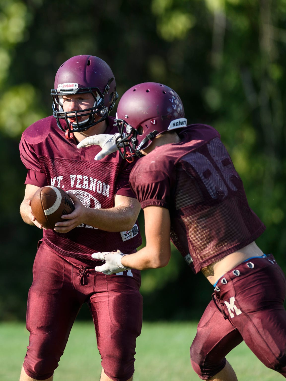 Mount Vernon Quarterback Rhett Snodgrass (7) makes a hand-off to teammate Sam Thomas (12) during an after school football practice at Mount Vernon High School in Mount Vernon, Ind., Tuesday, Sept. 18, 2018.