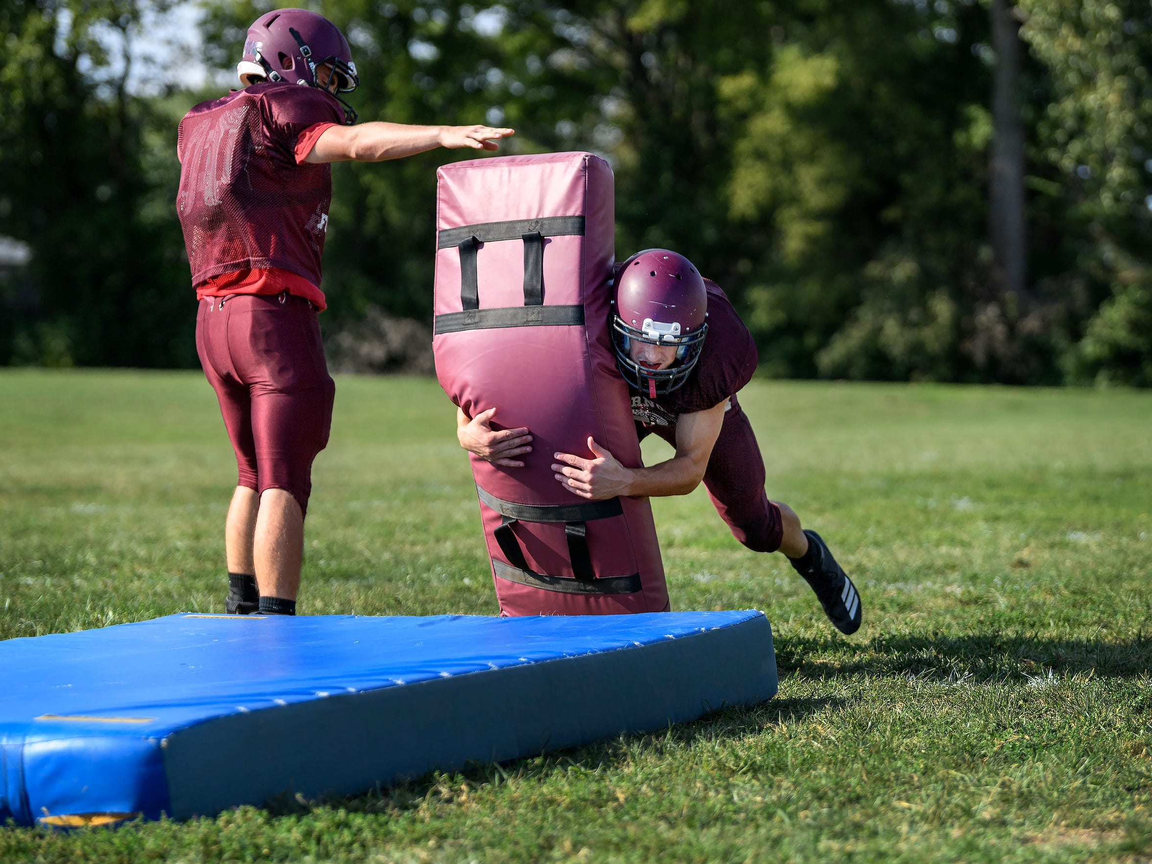 Mt. Vernon's Sam Thomas (12) dives hard into a pad as he practices tackling with his teammates at Mount Vernon High School in Mount Vernon, Ind., Tuesday, Sept. 18, 2018.