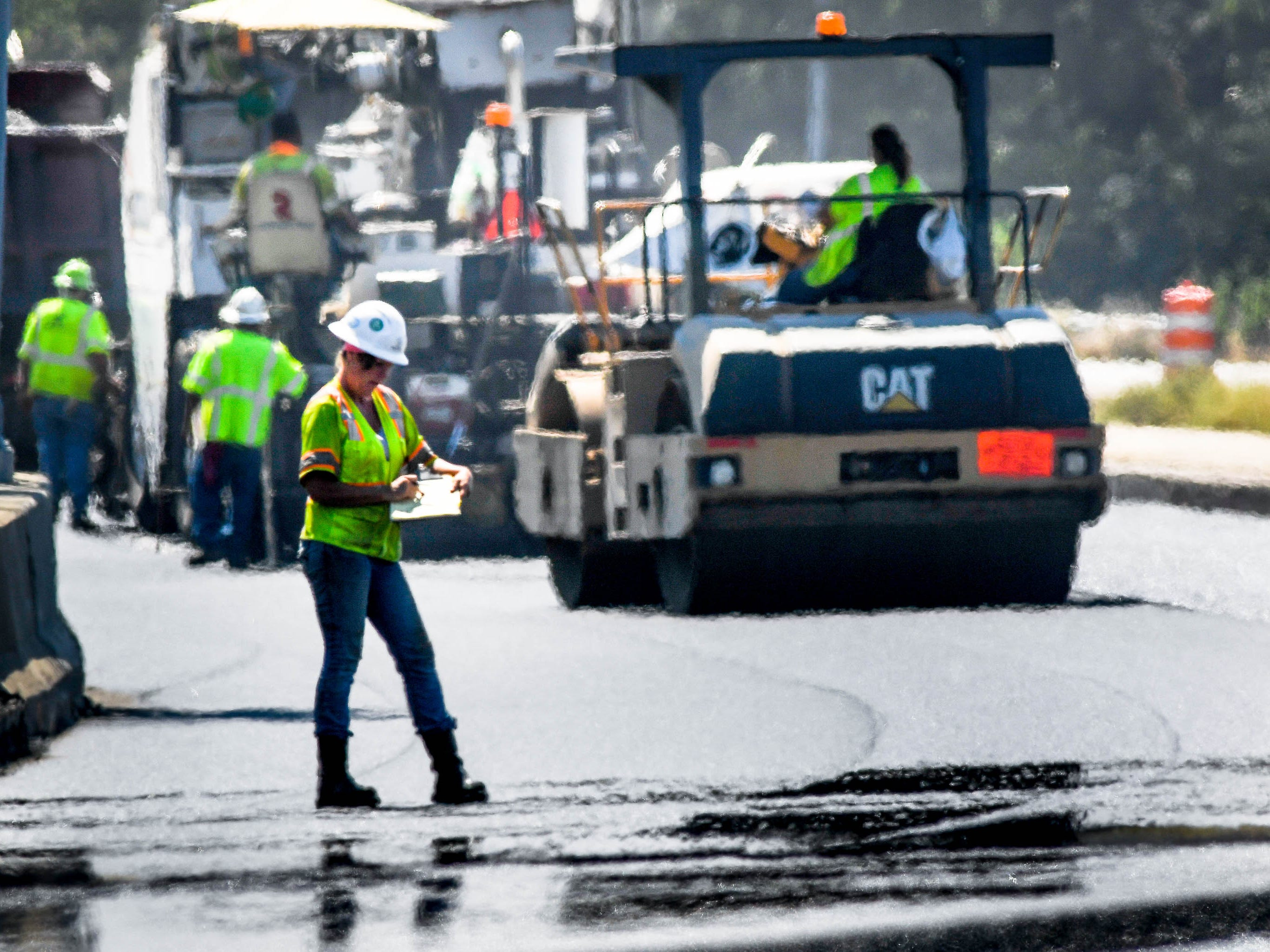 Heat shimmers off the pavement as E&B Paving worker Denise Davis writes down readings after gaging the depth of the freshly laid asphalt on the U.S. 41 bridge replacement project Thursday, September 20, 2018.