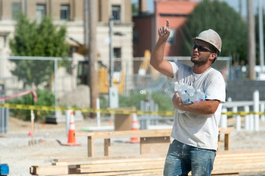 Tony Benton with Danco Construction carry bottles of water to coworkers on the site of the new Hyatt Place hotel in downtown Evansville Sept 19, 2018.