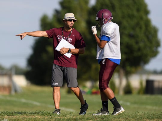 Mt. Vernon Head Coach Cory Brunson directs player Jaden Wilson (25) as they run plays during a football practice after school at Mount Vernon High School in Mount Vernon, Ind., Tuesday, Sept. 18, 2018.