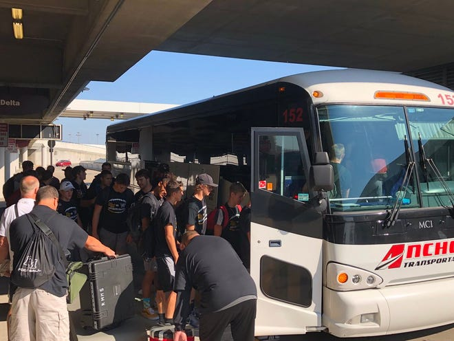 Rocky Mountain football team members  board a chartered bus for a ride from the airport in Nashville, Tennessee, to Bowling Green, Kentucky, on Thursday. The Lobos will play South Warren High School in Bowling Green on Friday night.