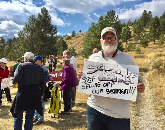 Bob Ronan, an employee of the Montana Wildlife Association, holds a sign at Thursday's rally.