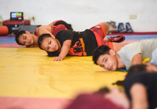 Simon Sanchez High School wrestlers, from top, Kaetlyn Quintanilla, Paulina Duenas and Gavin Whitt, stretch out their limbs before start drills along with other team members at a training gym in Yigo on Tuesday, Sept. 18, 2018.