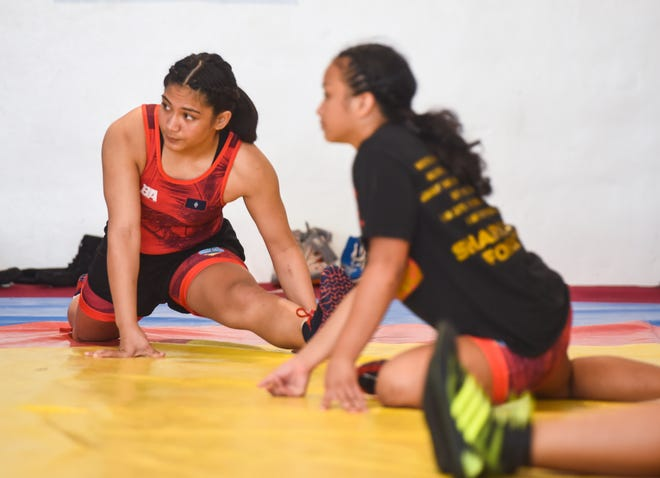 Kaetlyn Quintanilla, left, and Paulina Duenas, stretch before drills at a training gym in Yigo in this Sept. 18 file photo. The two said they can't wait to hit the mat at the Youth Olympics.