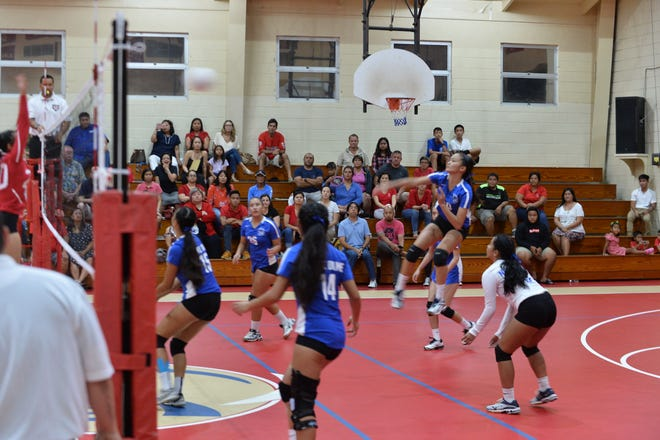 Minami Rabago in the air, goes for a back-row spike against the St. John's Knights on Sept. 19 at St. John's gym. The Royals won 2-1 to stay perfect at 11-0.