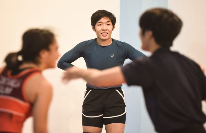 Seasoned wrestler Mia-Lahnee Aquino, center, observes a Simon Sanchez High School student  train with her sister at a private gym in Yigo on Tuesday, Sept. 18, 2018.