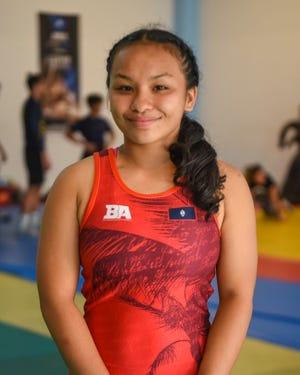 Simon Sanchez High School senior Paulina Duenas, 17, prepares to warm up with fellow wrestlers at their team's training gym in Yigo on Tuesday, Sept. 18, 2018.