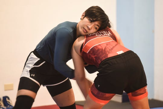 Seasoned wrestler Mia-Lahnee Aquino shares her experience as she demonstrates her wrestling skills with a Simon Sanchez High School student at a training gym in Yigo on Tuesday, Sept. 18, 2018.