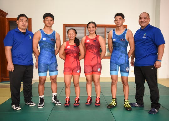 Wrestling coaches Tony Aquino, left, and Mariano Aquino, right, gather for a photo with Simon Sanchez High School wrestlers, from left, Lynch Santos, Paulina Duenas, Kaetlyn Quintanilla and Gavin Whitt at their team's training gym in Yigo on Tuesday, Sept. 18, 2018.