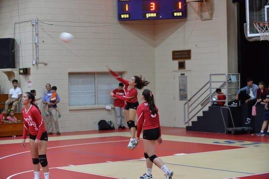 St. John's setter Hana Fernandez jump serves the ball against the Notre Dame Royals Sept. 19 at the Knights gym.