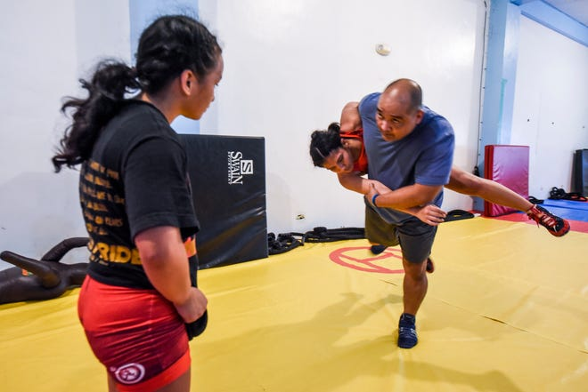 Paulina Duenas, left, observes as wrestling coach Mariano Aquino executes a hip throw to take down wrestler Kaetlyn Quintanilla during a training seesion in Yigo on Sept. 18, 2018.
