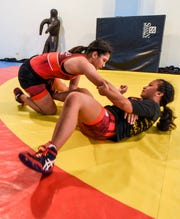 Simon Sanchez High School wrestlers, Kaetlyn Quintanilla, left, and teammate Paulina Duenas, run through drills together at their team's training gym in Yigo on Tuesday, Sept. 18, 2018.