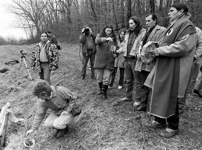 Bystanders take part in a tobacco-burning ceremony at the Slack farm near Uniontown in January 1988, as Indian leaders, including activist Dennis Banks (R), chant and play a drum at the site where hundreds of Indian graves were desecrated.