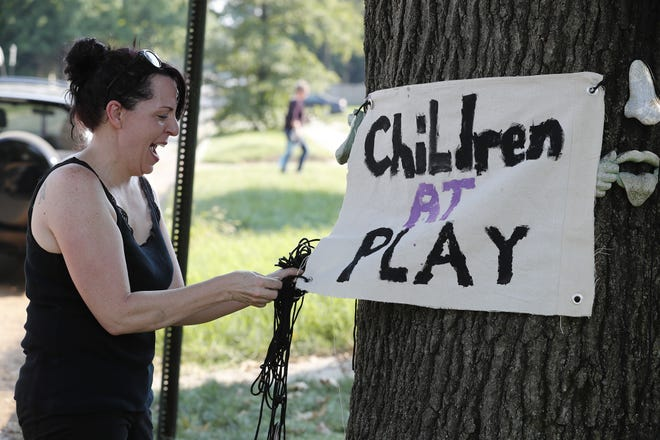 Rachael Kissinger places a homemade sign across from her home near the intersection of Carrollton Avenue and East 27th Street on Thursday, Sept. 20, 2018. The once-quiet one-way street has been inundated with a constant stream of commuters since the closing of the College Avenue bridge.