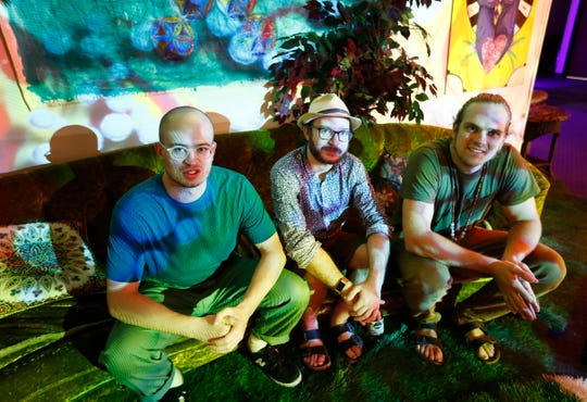 Ben Sutphin, from left, Matt Panfil and Colin Oakley pose under a morphing display of lights at the Healer, an all-ages, interactive art and music venue, Thursday, Sept. 20, 2018.