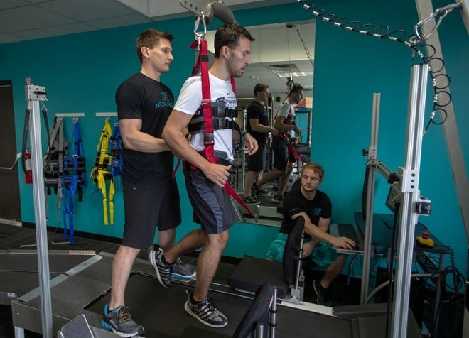 Bart Richwalski (left), a Neurological Rehabilitation Exercise Specialist at NeuroHope, and Marshall Sparenberg (right), a Physical Therapy Tech., help Ryan Bardellini, who suffered a life threatening head injury after he fell out of a moving SUV last November, and is on path to recovery, Indianapolis, Thursday, Sept. 20, 2018. Bardellini graduated this past Spring from International School of Indiana and has plans to attend Purdue in Fall of 2019.