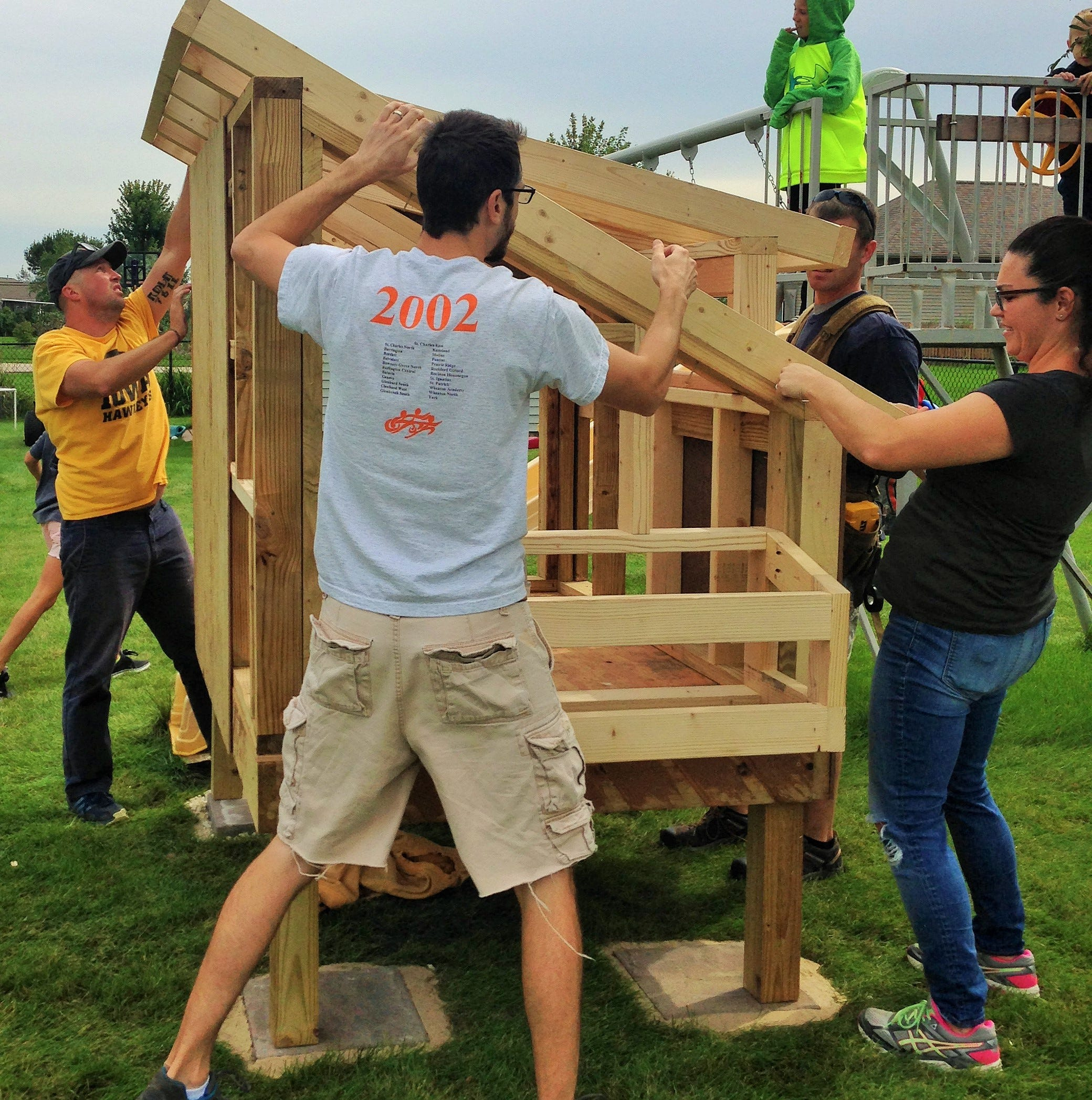 """In their own version of an Amish barn-raising, North Liberty neighbors of the Carne family recently conducted a """"coop-raising"""" to help erect this urban chicken house.  Working from left are Tony Hakes, Clint Carne, Amy Schultz and Mark Bennett."""
