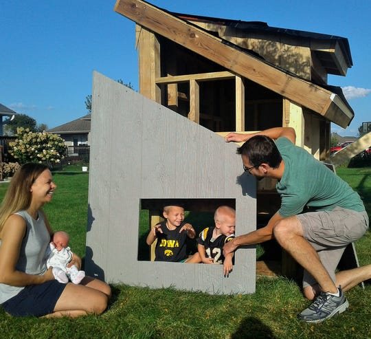 This new urban chicken coop under construction in the Fox Run area of North Liberty is a family project of the Carne family.  From left are Kristi holding Hazel, Cade, Archer and Clint.