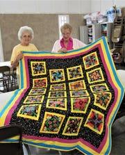"Linda Osborne and Agnes Miranda show off a full quilt they refurbished after it was donated by a church member. ""It will be useful for another family again,"" said Osborne."