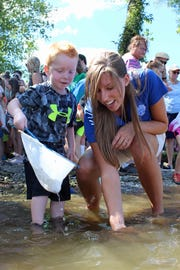 Meredith Harris, Tennessee Aquarium Conservation Institute reintroduction biologist, helps a child release baby lake sturgeon.