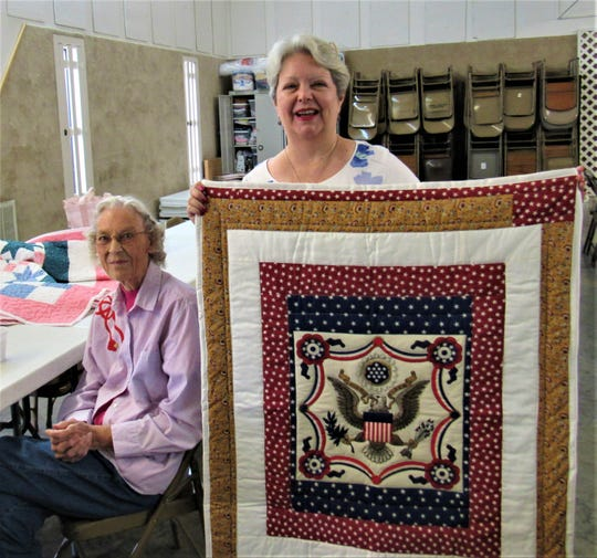 Charter member Mary Mathis watches as Brenda Nelson displays a lap quilt she made for a military veteran.